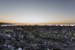 Tramonto dell'oceano con la siluetta di pietra impilata fotografia stock libera da diritti