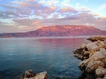 Tramonto della montagna in rosso contro lo sfondo del mare e fotografia stock libera da diritti