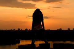 Tramonto della ragazza sulla città vicino al fiume fotografie stock
