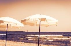 Tramonto della Sicilia, vista della spiaggia del mare ionico vicino a Catania, lido Cled con gli ombrelli bianchi immagini stock