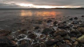 Tramonto della spiaggia alla spiaggia di pietra fotografia stock