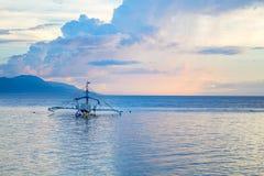 Tramonto della spiaggia con le nuvole arancio e blu Mare tropicale ed isola distante nei colori di tramonto Fotografia Stock Libera da Diritti