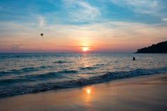 Tramonto della spiaggia di panorama con il nuoto i del viaggiatore Immagine Stock