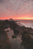 Tramonto della spiaggia rocciosa Immagine Stock