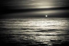 Tramonto di alba sopra le onde di oceano del mare in bianco e nero Immagini Stock