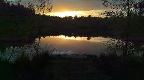Tramonto di autunno dietro gli alberi e refelected su acqua Fotografie Stock Libere da Diritti