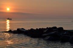 Tramonto di estate sopra il mare Barca e pietre Fotografie Stock
