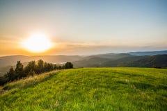 Tramonto di estate su un prato verde in montagne Fotografie Stock