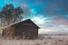 Tramonto di inverno dietro una vecchia Camera del granaio Immagine Stock