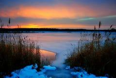 Tramonto di inverno su un lago congelato Immagini Stock