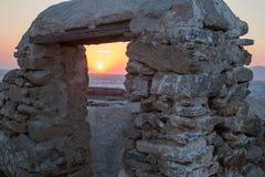 Tramonto di Mykonos tramite il portone di pietra Immagine Stock