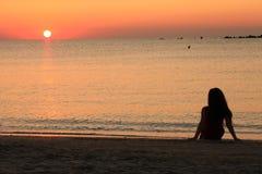 Tramonto di sorveglianza della ragazza sulla spiaggia Fotografie Stock