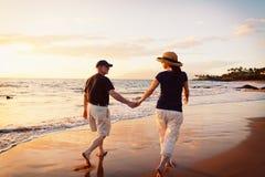Tramonto di sorveglianza delle coppie alla spiaggia fotografie stock libere da diritti
