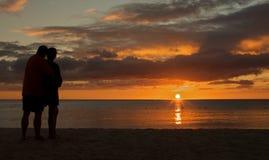 Tramonto di sorveglianza delle coppie sulla spiaggia Immagini Stock