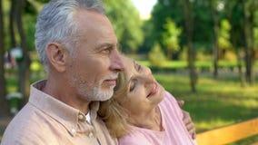 Tramonto di sorveglianza in parco, matrimonio felice romanzesco, campagna di rilassamento delle vecchie coppie immagini stock