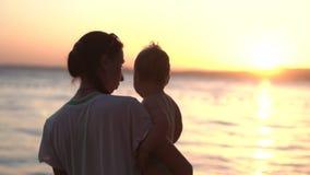 Tramonto di stupore - la madre con il bambino sulle sue mani cammina sulla spiaggia al rallentatore archivi video