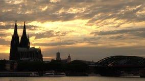 Tramonto dietro la cattedrale ed i treni di Colonia sul ponte di Hohenzollern sopra il fiume il Reno, Germania video d archivio