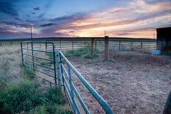 Tramonto dietro la recinzione e granaio in pianure orientali Colorado immagine stock