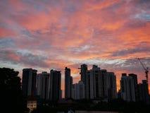 Tramonto dietro le costruzioni con il bello cielo nuvoloso fotografie stock