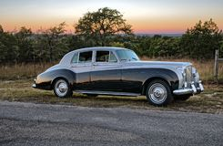 Tramonto dietro le limousine d'annata di luxery su una strada campestre del Texas Fotografia Stock