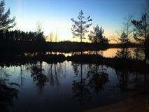 Tramonto dietro un lago Fotografia Stock