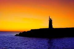 Tramonto dorato di alba in faro rosso del falò del mare Immagini Stock Libere da Diritti