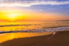 Tramonto dorato di alba sopra le onde di oceano del mare Fotografia Stock