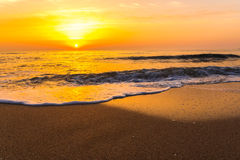 Tramonto dorato di alba sopra le onde di oceano del mare Immagine Stock