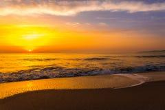 Tramonto dorato di alba sopra le onde di oceano del mare Immagini Stock