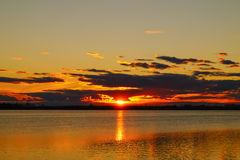 Tramonto dorato di riflessione sopra il fondo del lago Fotografia Stock