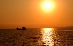 Tramonto dorato e siluetta della nave Immagini Stock Libere da Diritti
