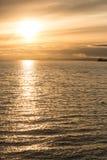 Tramonto dorato in mare Immagine Stock