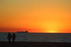 Tramonto dorato sulla spiaggia Immagini Stock