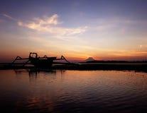 Tramonto drammatico ad una spiaggia con un catamarano e un supporto Agung fotografie stock libere da diritti