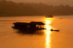 Tramonto e barca con la casa di galleggiamento fotografie stock libere da diritti