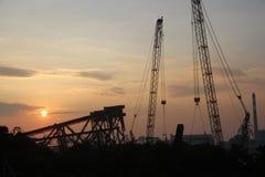 Tramonto e macchinario del porto Immagine Stock