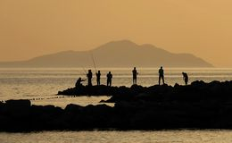 Tramonto e pescatori Immagini Stock Libere da Diritti