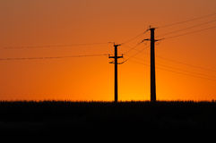 Tramonto e piloni elettrici Fotografie Stock