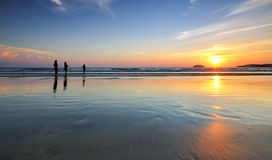 Tramonto e siluette alla spiaggia Immagini Stock Libere da Diritti