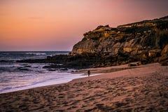Tramonto fantastico nel paesaggio, con la scogliera e rocce e surfista che camminano lungo il mare sulla spiaggia di São Lourenà immagine stock