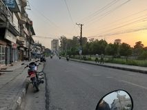 Tramonto intorno ad una strada di grande traffico Vista parcheggiata della bici fotografia stock