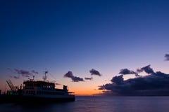 Tramonto in mare con un traghetto nel porto fotografie stock