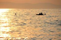 Tramonto in mare, rotture annuali, nuoto e immagine stock