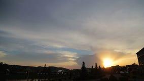 Tramonto meraviglioso sopra la città Il sole va giù e forma un cielo brillante Tramonto sopra i tetti e gli alberi stock footage