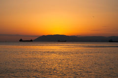 Tramonto naturale del mare di estate Siluette delle navi e della striscia di terra sull'orizzonte Immagini Stock Libere da Diritti