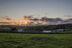 Tramonto nei campi dell'azienda agricola con il bello cielo nuvoloso, Cornovaglia, Regno Unito Fotografia Stock Libera da Diritti
