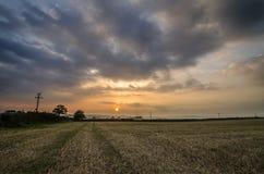 Tramonto nei campi dell'azienda agricola con il bello cielo nuvoloso, Cornovaglia, Regno Unito Fotografie Stock Libere da Diritti