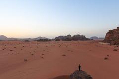 Tramonto nel deserto di Wadi Rum, Giordania, con un uomo che guarda la scena da una roccia su priorità alta Immagini Stock