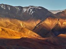 Tramonto nelle alte montagne: gli ultimi raggi del sole colorano i pendii delle colline in un colore arancio luminoso, sulla bugi Fotografie Stock Libere da Diritti