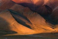 Tramonto nelle alte montagne: i pendii marroni enormi delle montagne sono dipinti con il sole in un colore caldo arancio, al bott Fotografie Stock Libere da Diritti